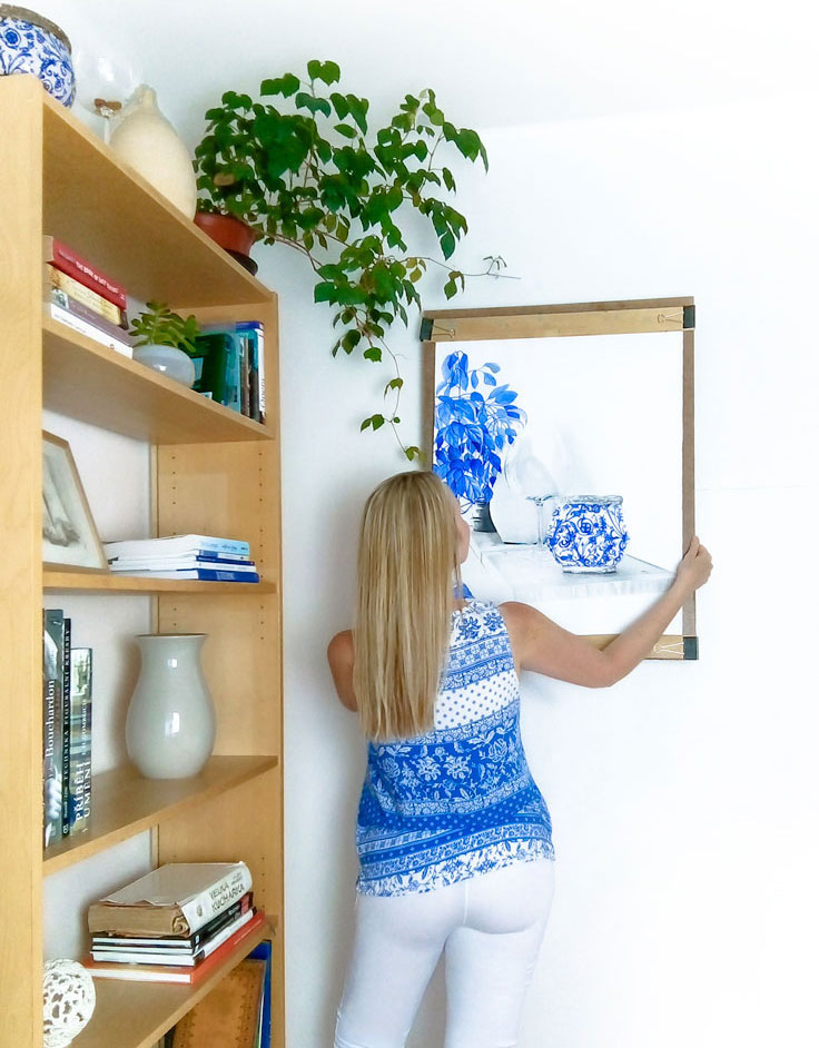Blonde woman hanging artwork